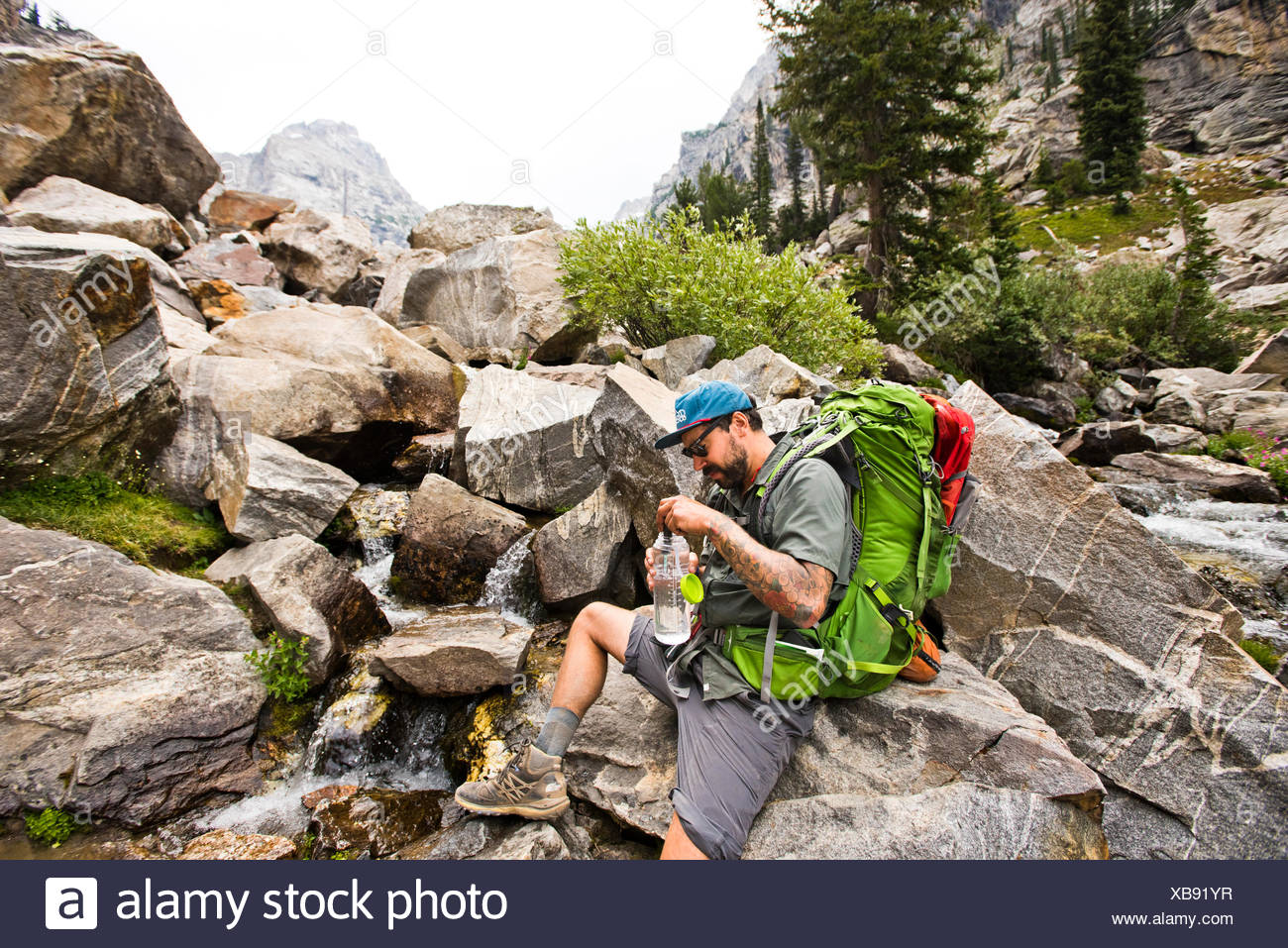 A hiker stops to fill his water bottle. - Stock Image