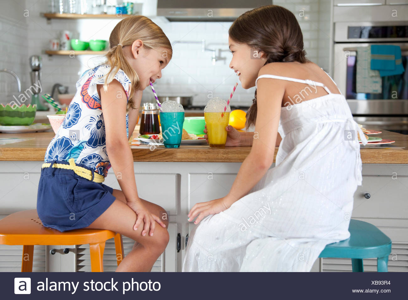 Two mischievous sisters blowing bubbles through straws at breakfast bar - Stock Image