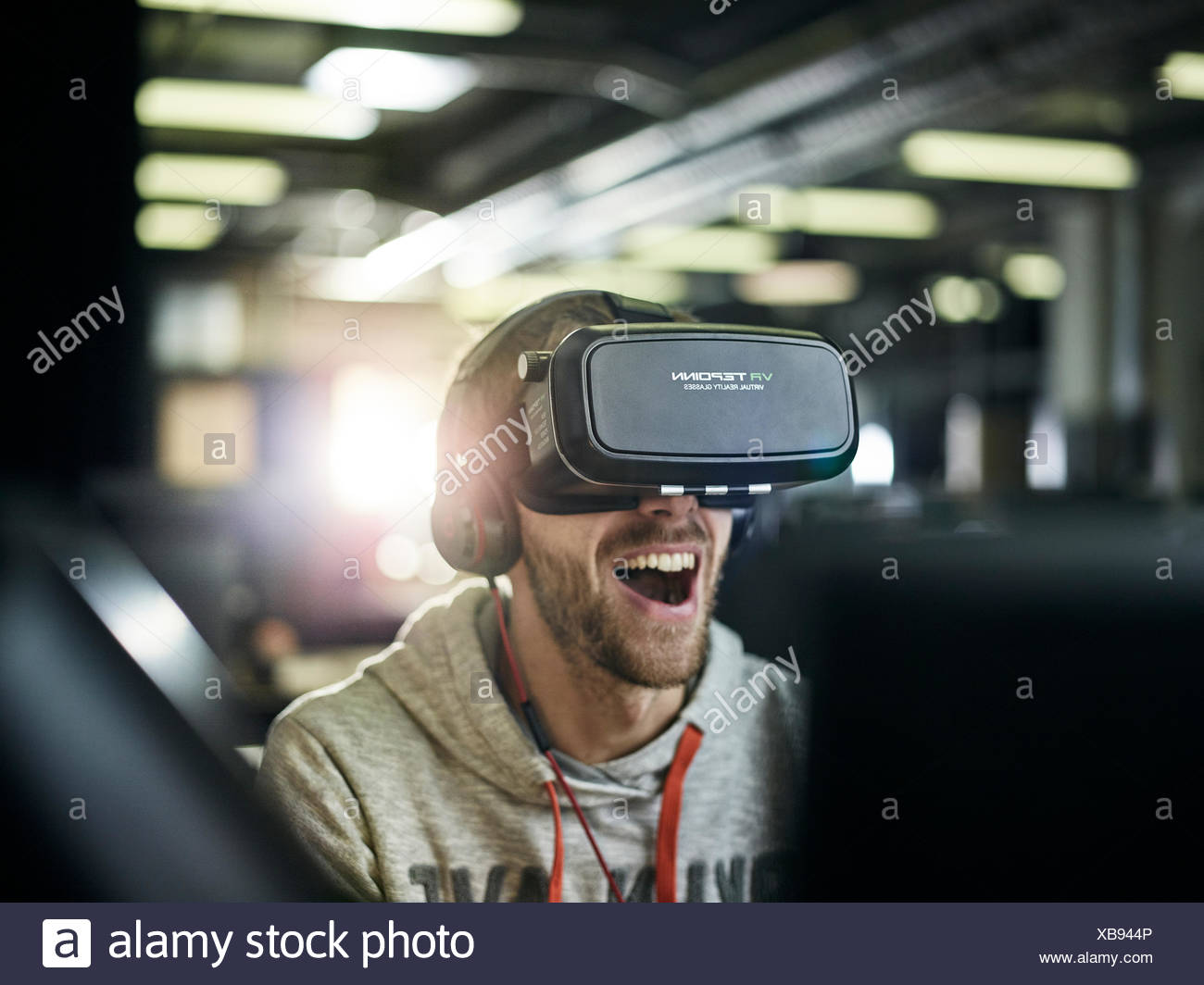 Man with VR goggles, virtual reality glasses and headphones - Stock Image