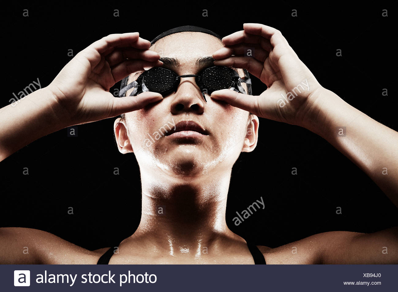 Young woman putting on swimming goggles - Stock Image