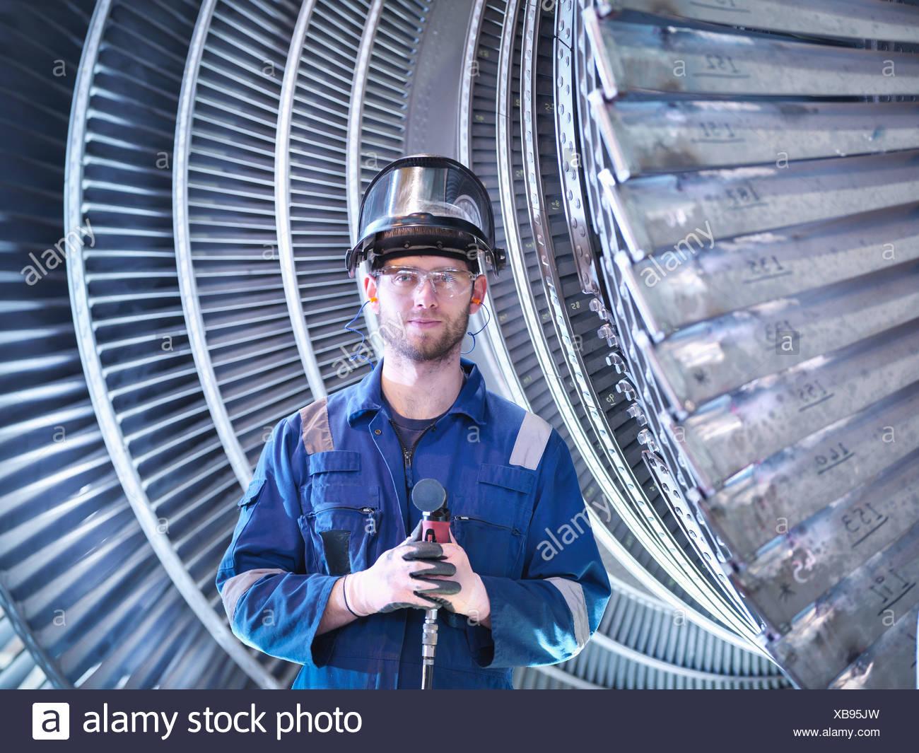 Portrait of apprentice engineer in steam turbine repair workshop - Stock Image