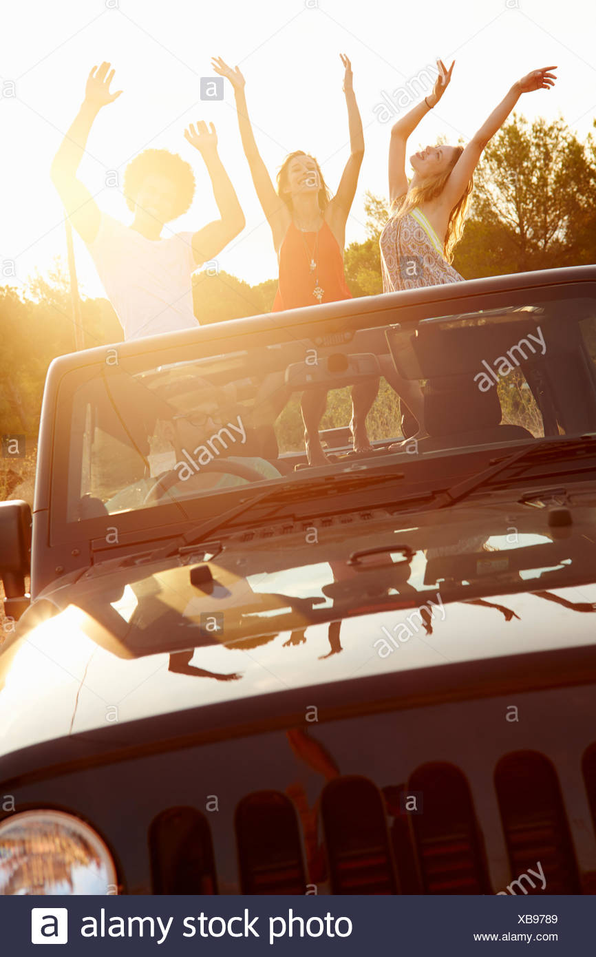 Three Women Dancing In Back Of Open Top Car - Stock Image