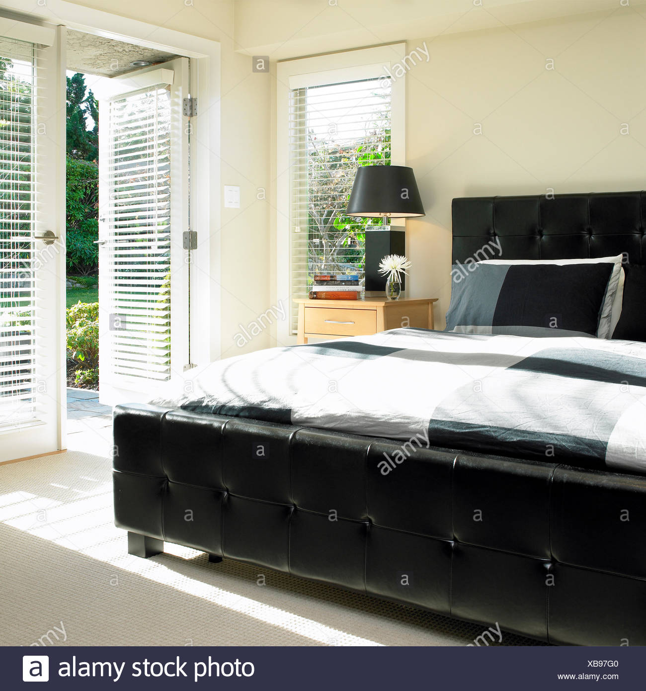 Bedroom With Black Leather Tufted Headboard And French Doors To Garden Stock Photo Alamy