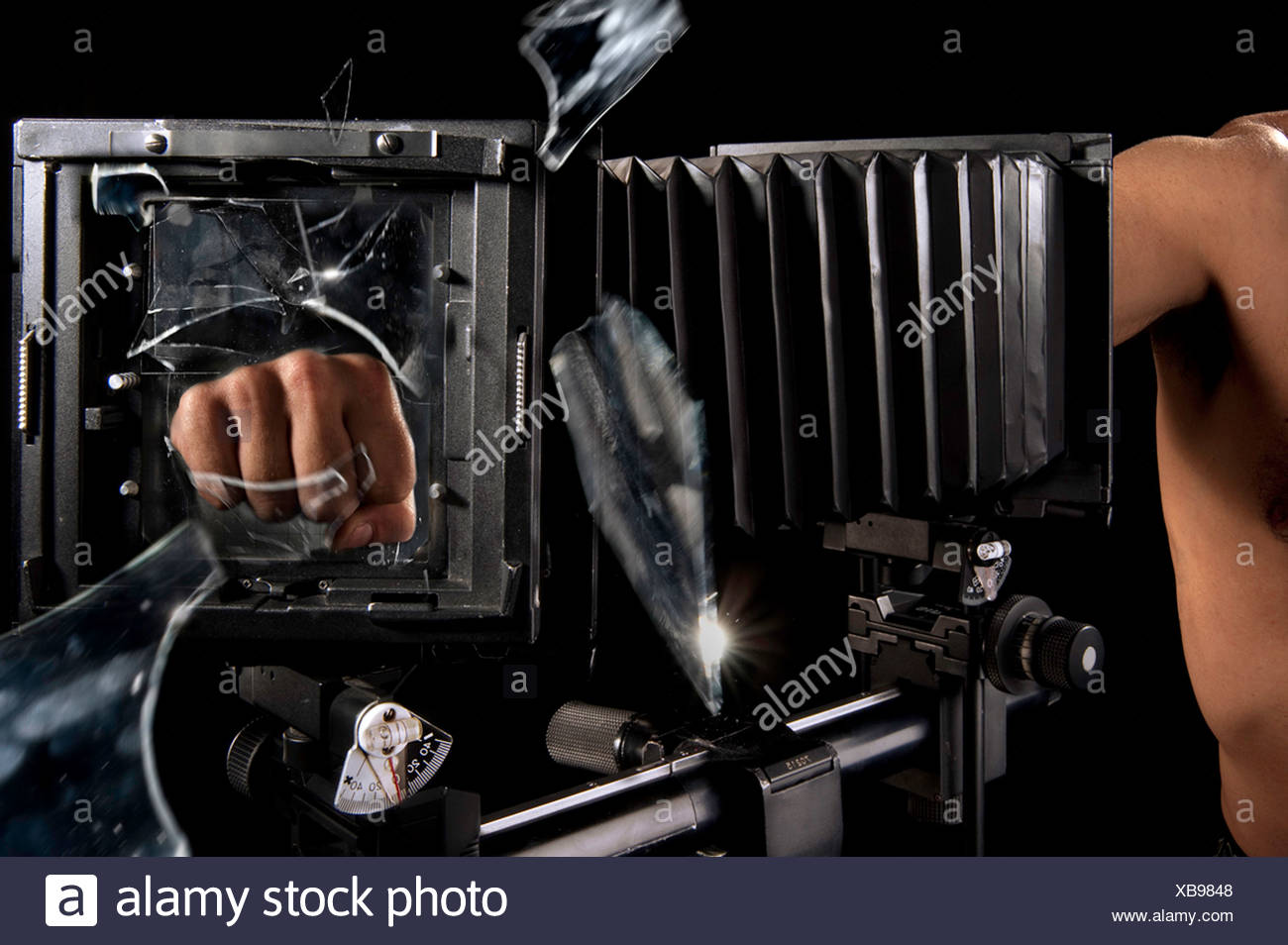Fist smashes glass - Stock Image