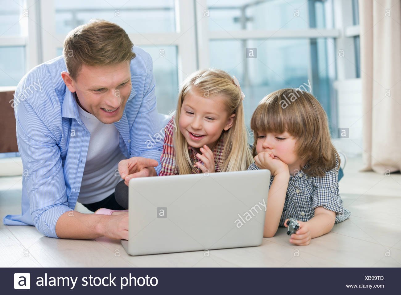 Happy father showing something to children on laptop at home - Stock Image