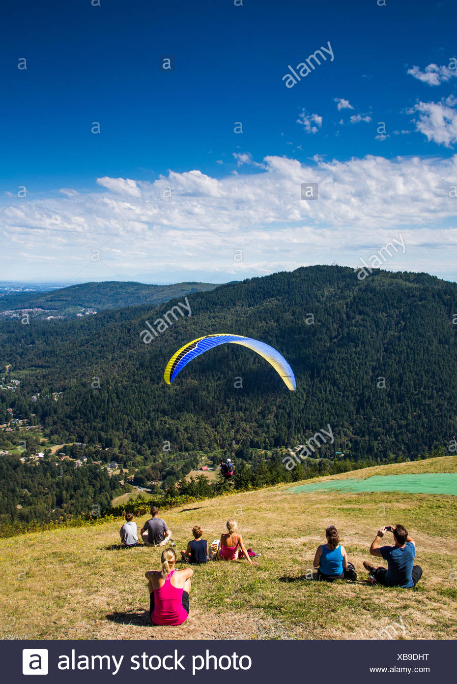Poo Poo Point is a tourist attraction near Issaquah, WA where hang gliders launch into the clear sky above a thick green forest. - Stock Image