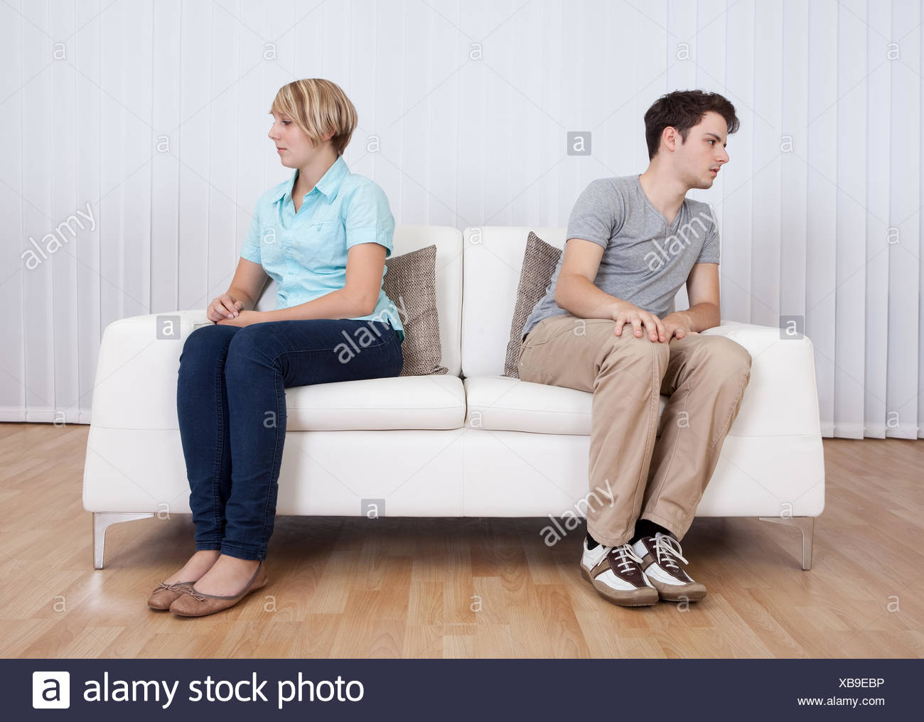 Brother and sister have had an argument and are sitting at opposite ends of a sofa - Stock Image