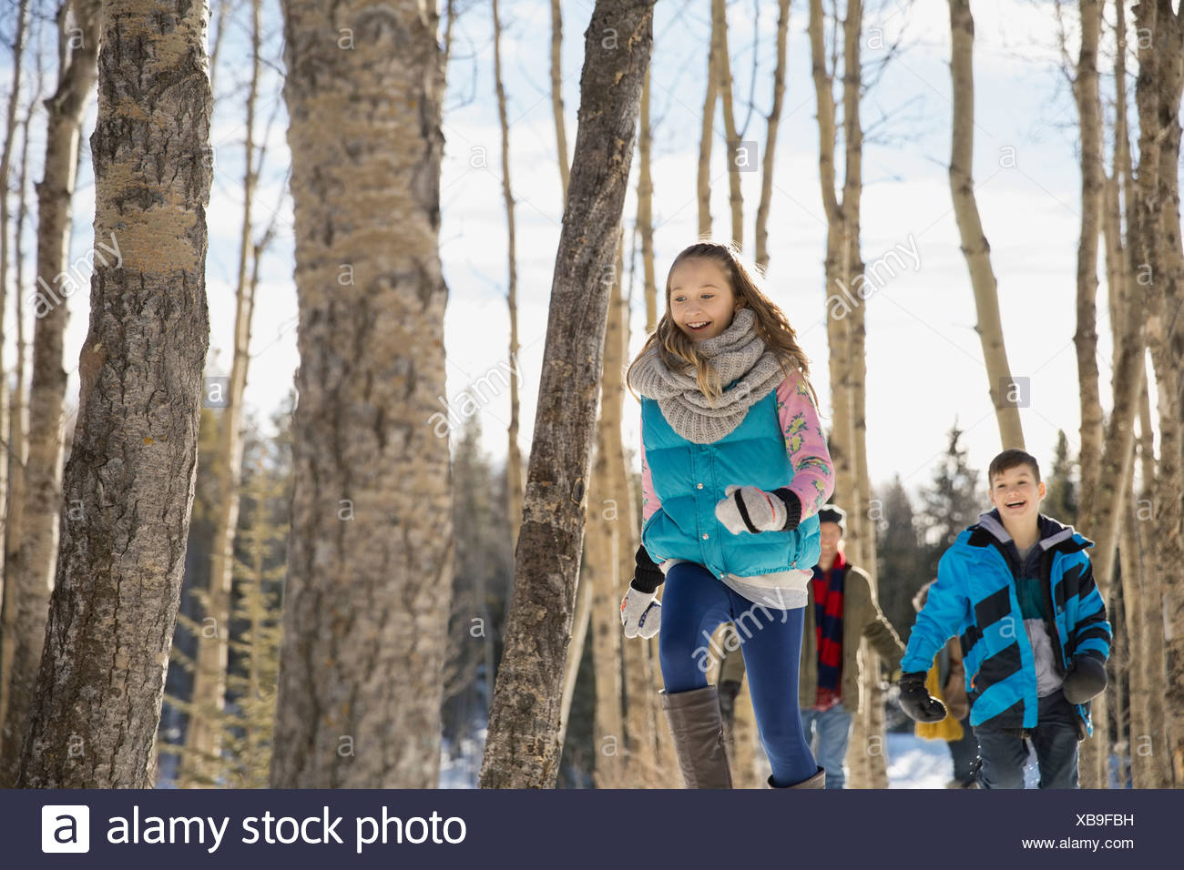Siblings running through winter forest - Stock Image