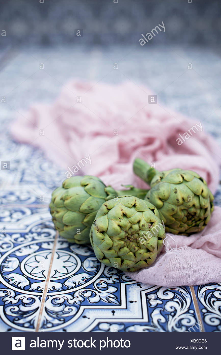 Artichoke heads on a tiles kitchen table - Stock Image