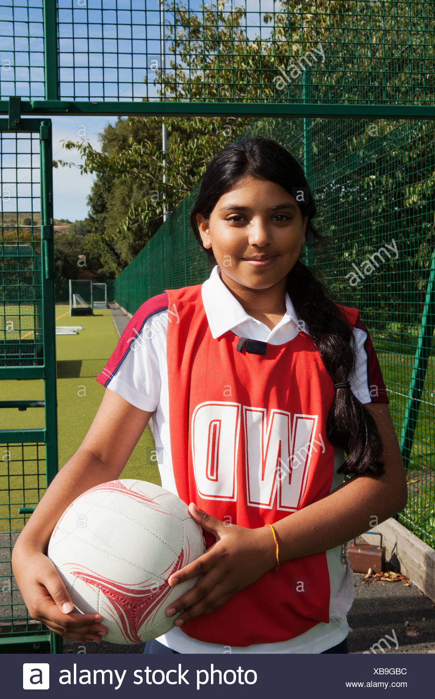 Portrait of schoolgirl netball player with ball - Stock Image