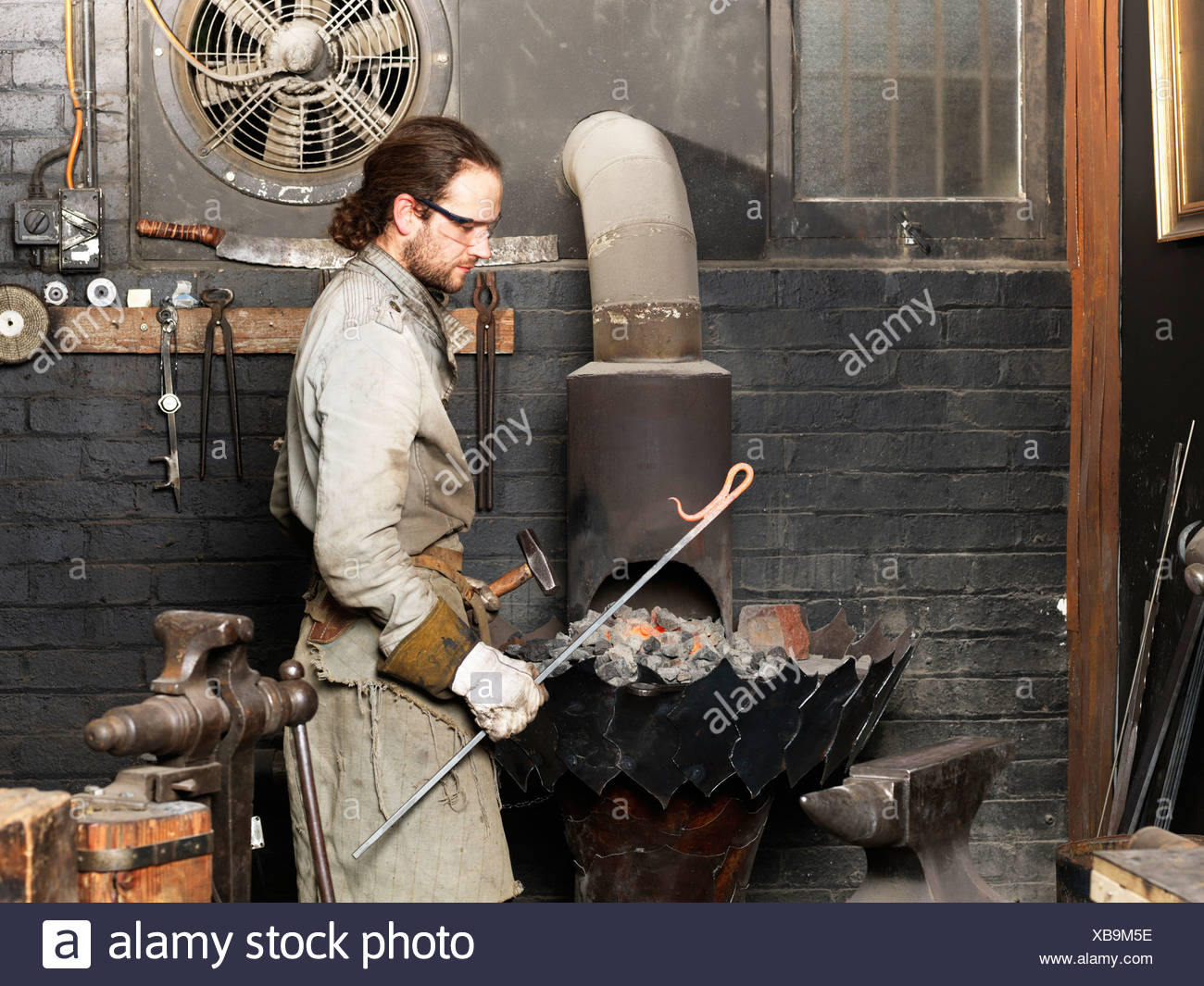 Blacksmith with a red hot metal rod in workshop - Stock Image