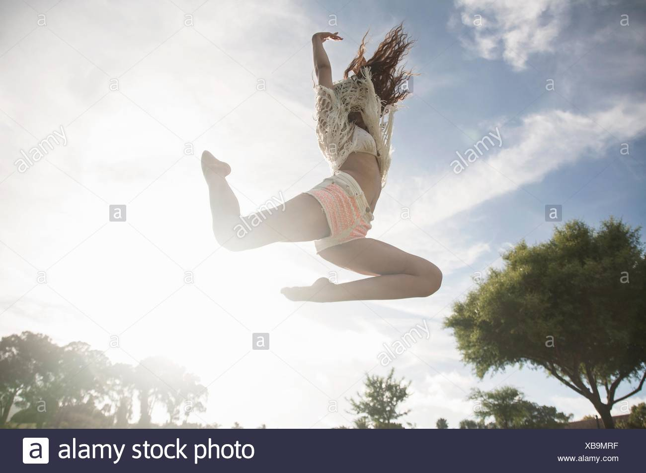 Low angle view of young woman jumping in mid air, arms raised - Stock Image