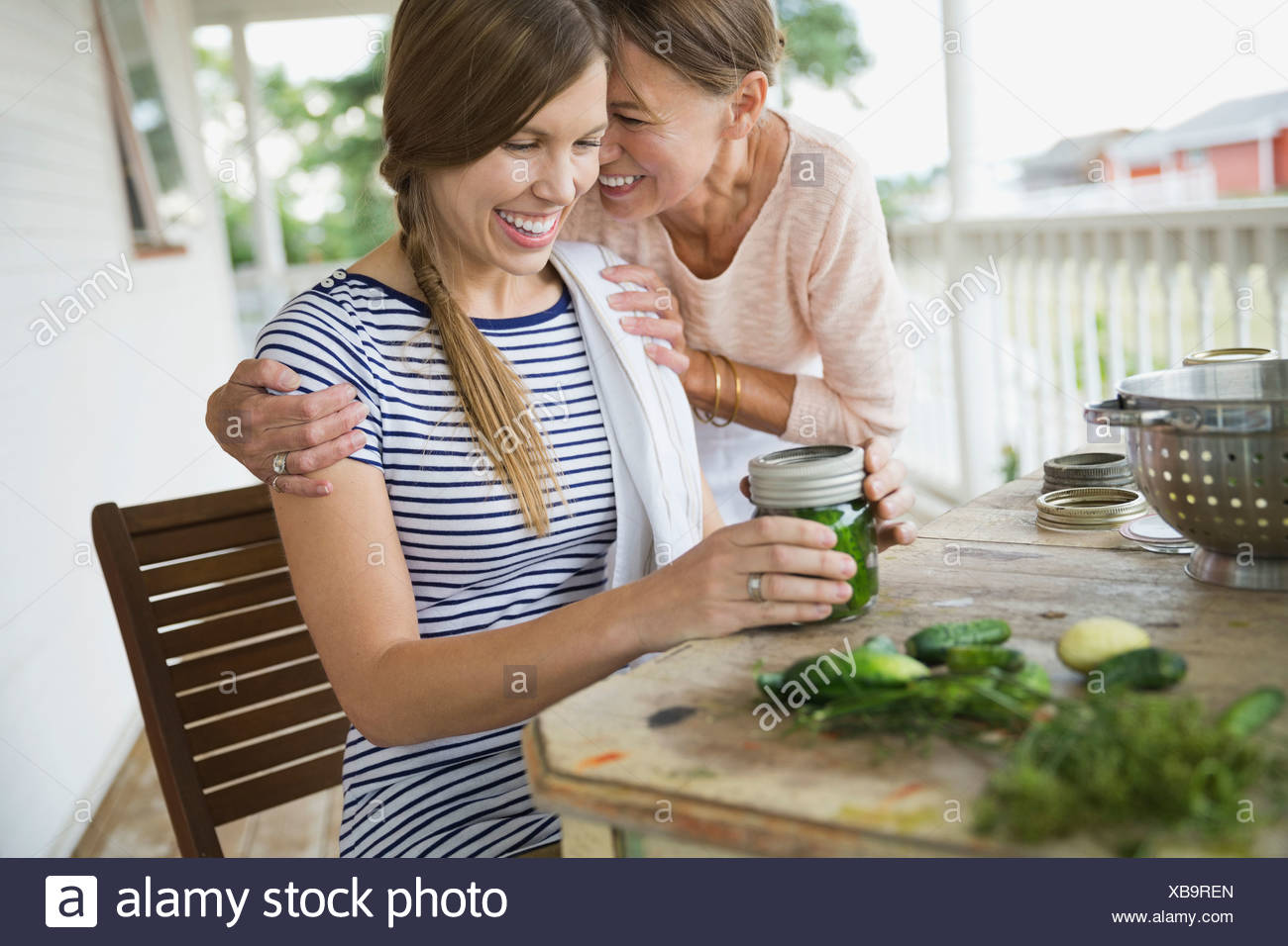 Affectionate mother and daughter canning vegetables - Stock Image