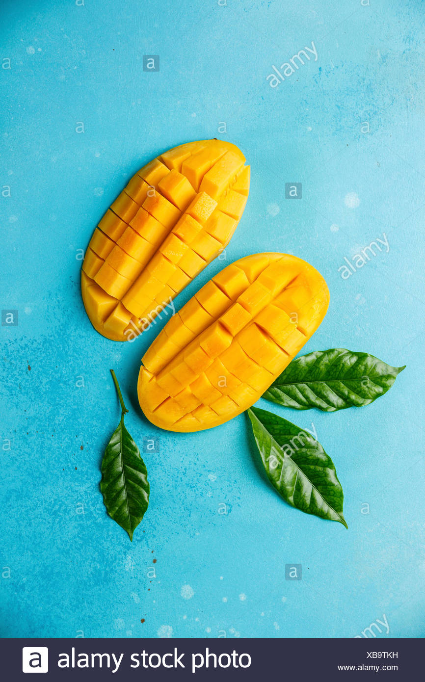 Raw fresh sliced mango on blue background - Stock Image