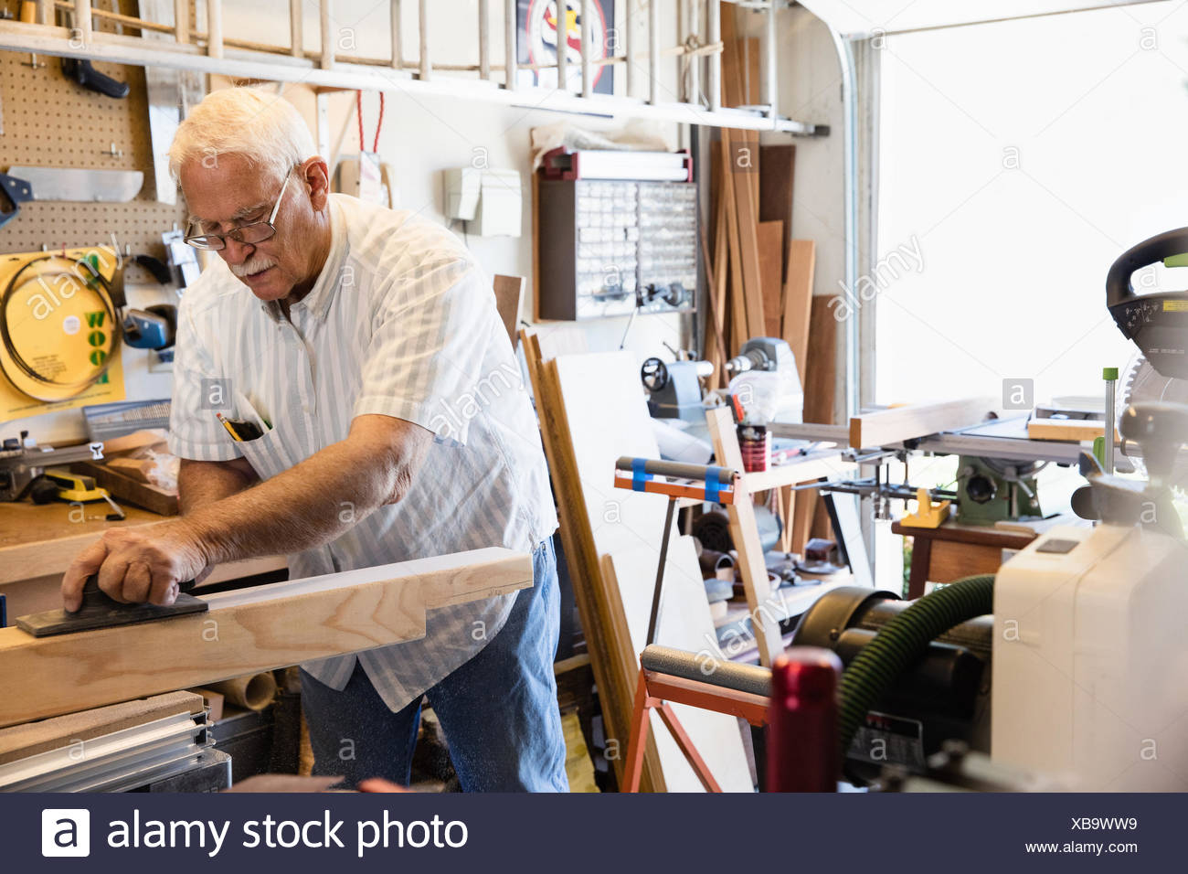 Senior man planing woodblock in carpentry workshop - Stock Image