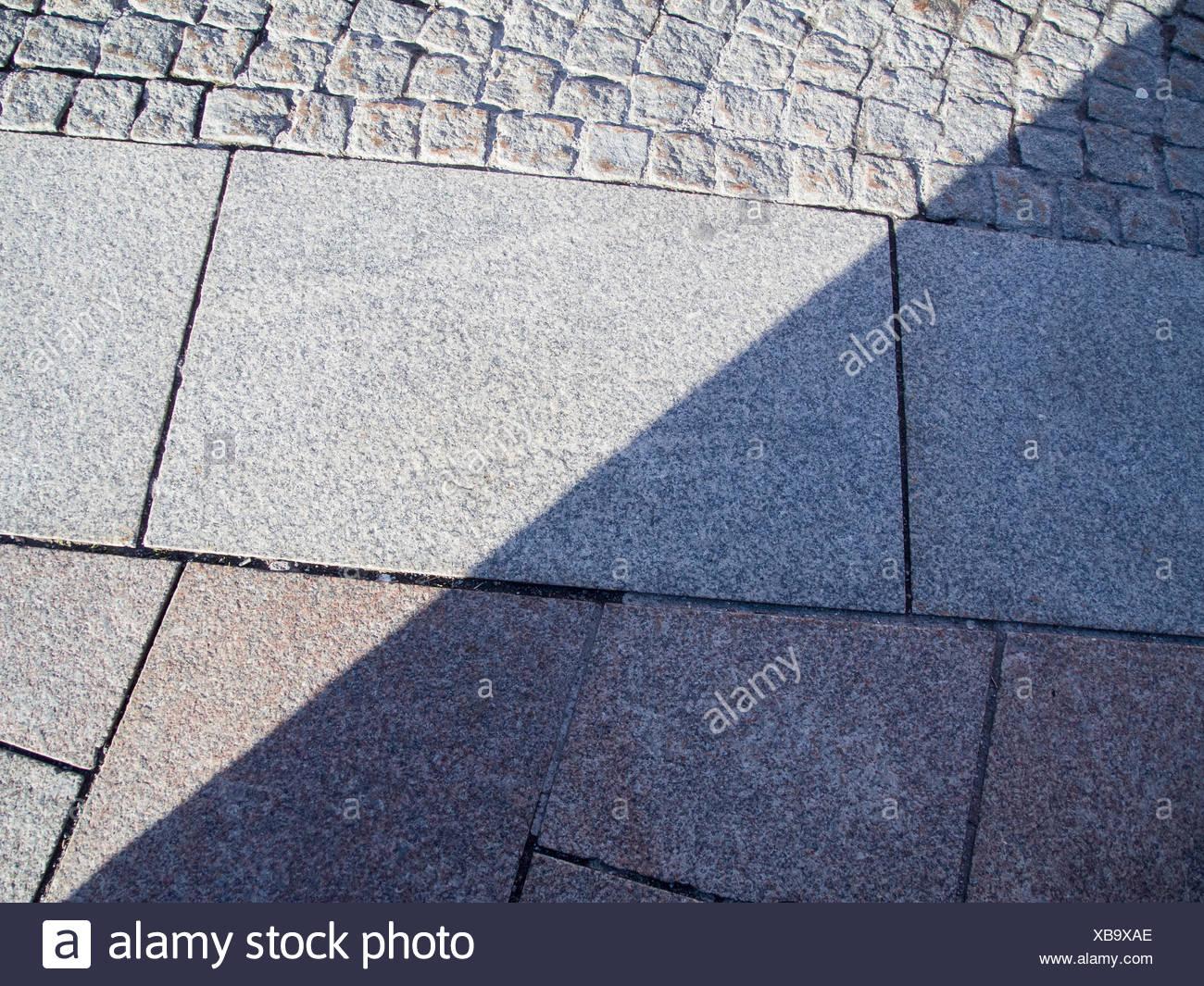 formatfüllende Ansicht verbauter unterschiedlicher Pflastersteine und Gehwegplatten mit teilenden Schatten - Stock Image