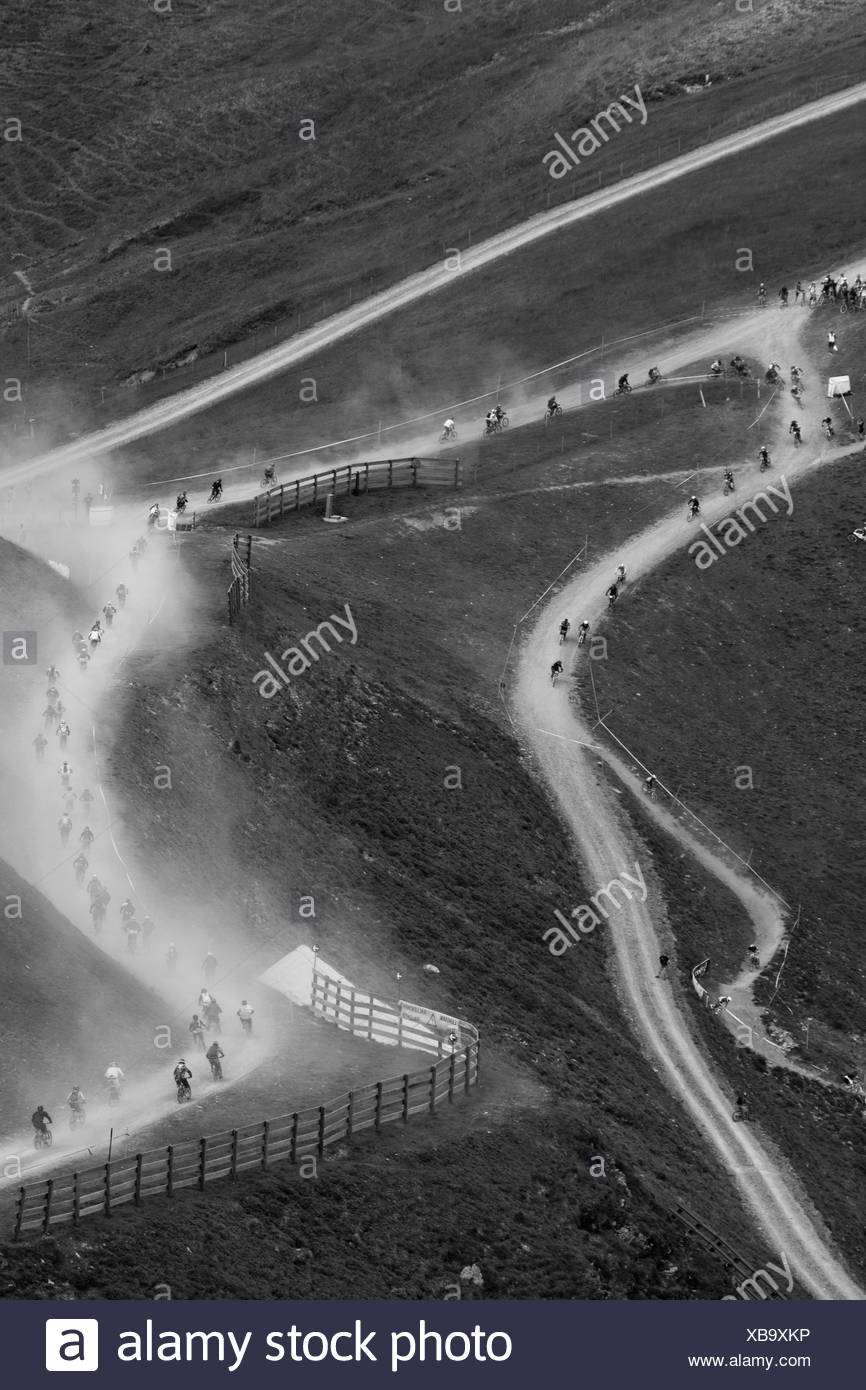 Austria, Salzburger Land, Hinterglemm, View of mountainbike downhill race on dusty gravel road - Stock Image