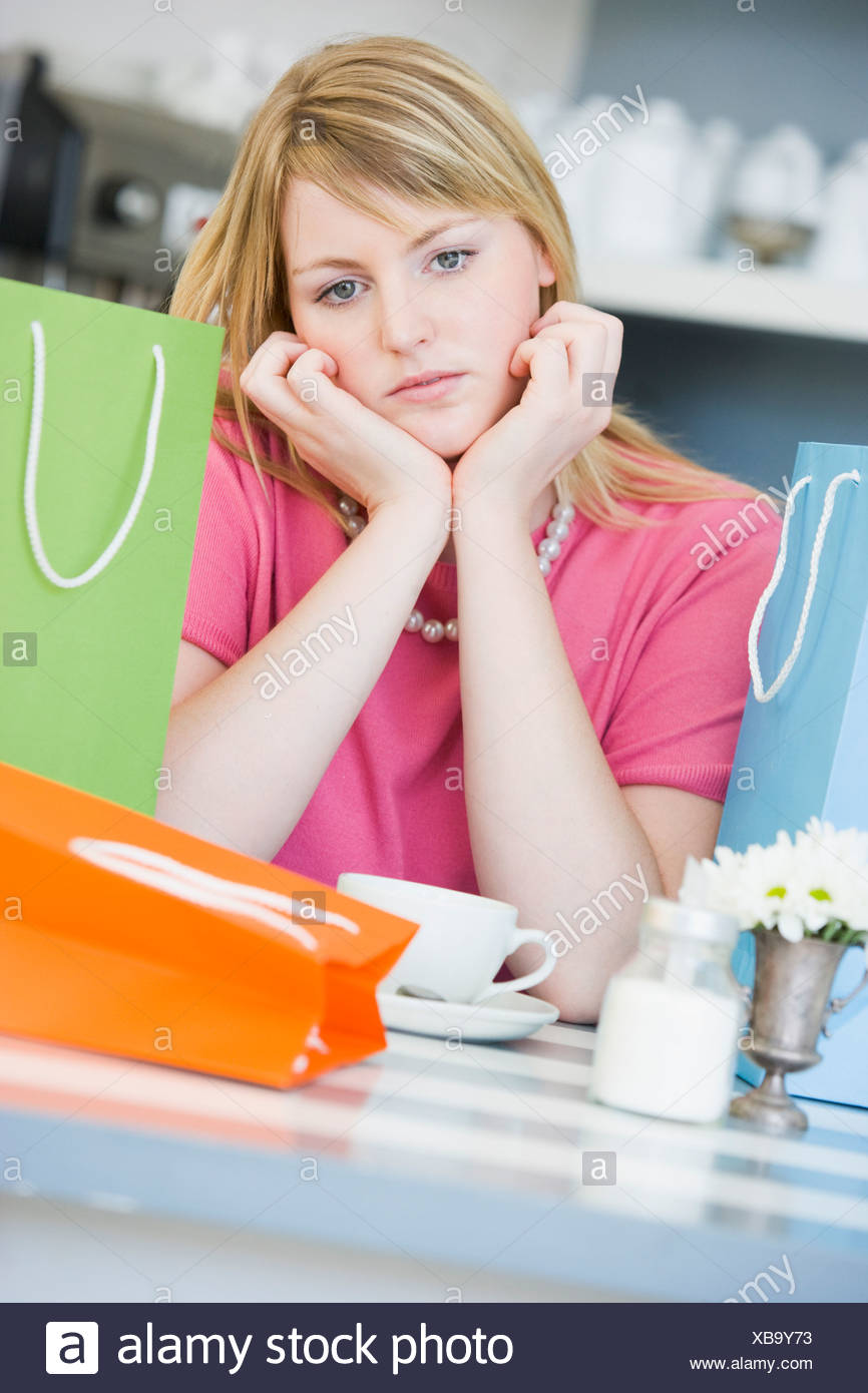 Young woman sitting at a table taking a break from shopping and drinking tea - Stock Image