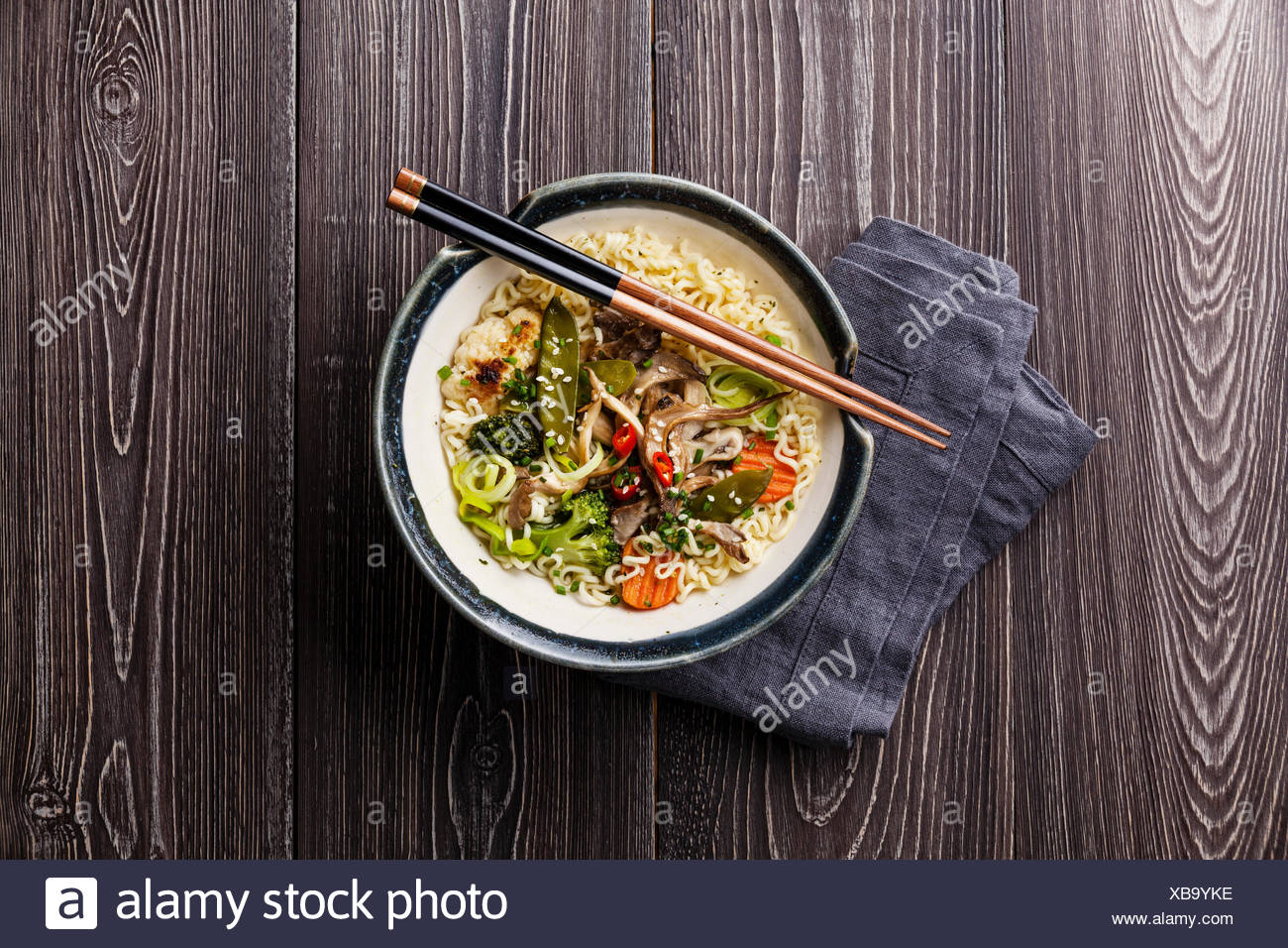 Asian noodles with oyster mushrooms and vegetables in bowl on gray wooden background - Stock Image