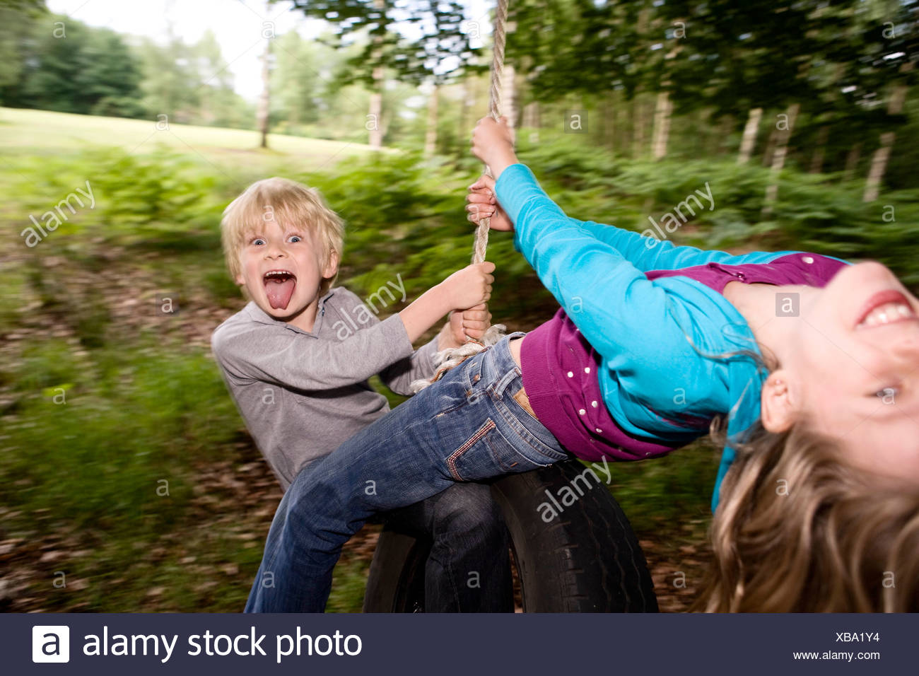 Boy and girl on tire swing Stock Photo