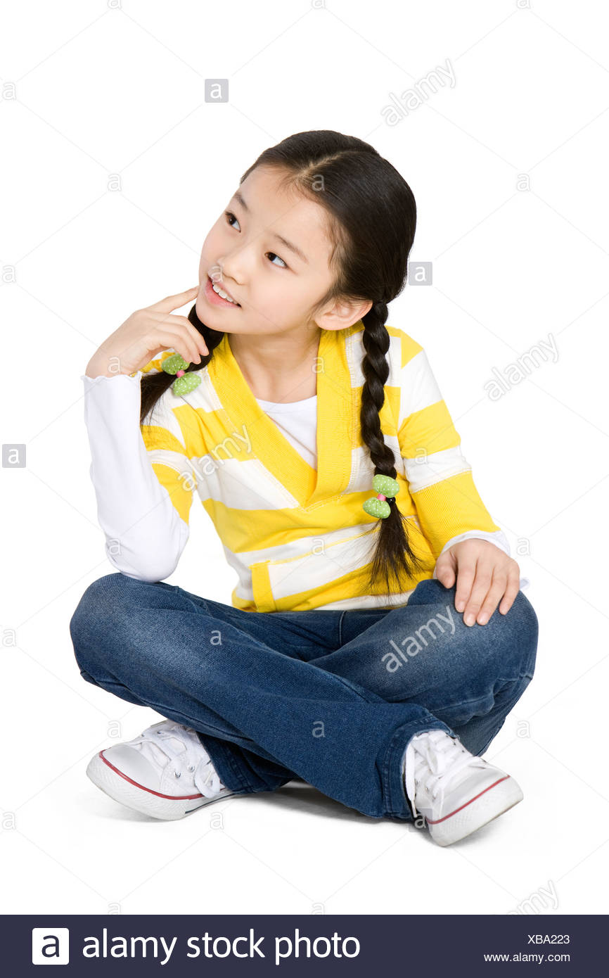 Young girl sitting crossed legged thinking - Stock Image