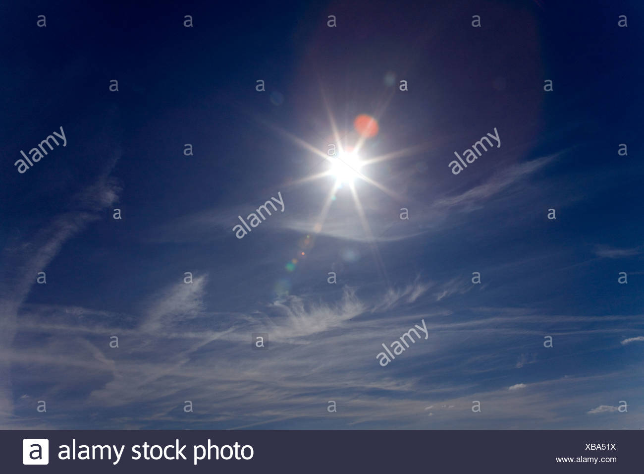 Sun shining in blue sky - Stock Image