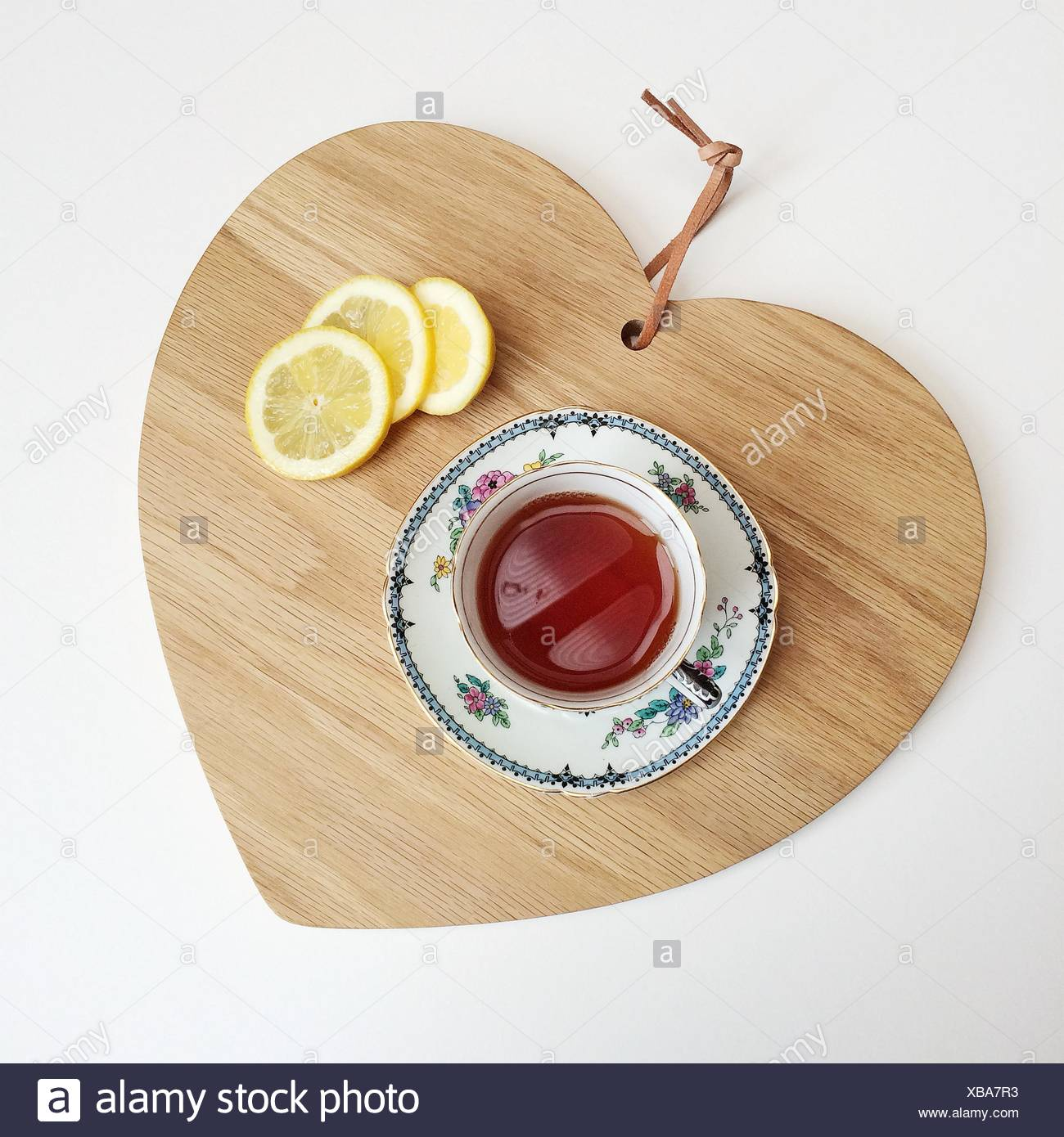 Tea and lemon slices on a chopping board Stock Photo