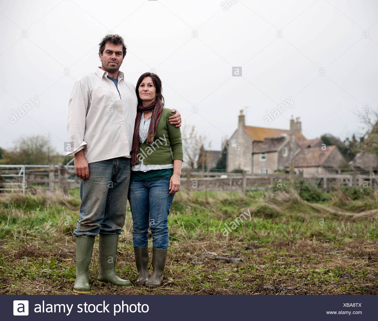 couple standing in front of farm house Stock Photo