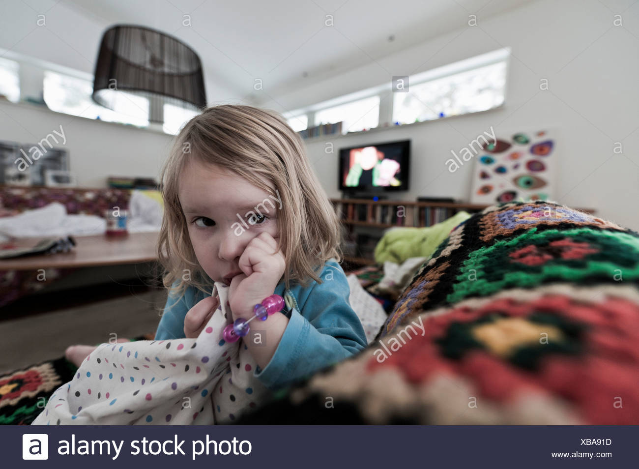 Blond haired girl sucking thumb while resting on sofa - Stock Image
