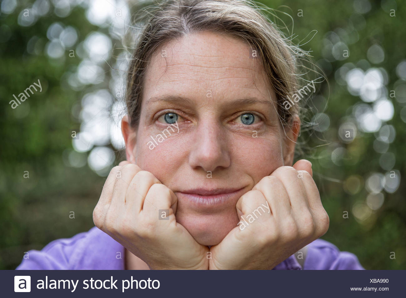Woman, early 40's, supporting her head with her hands, looking interested - Stock Image