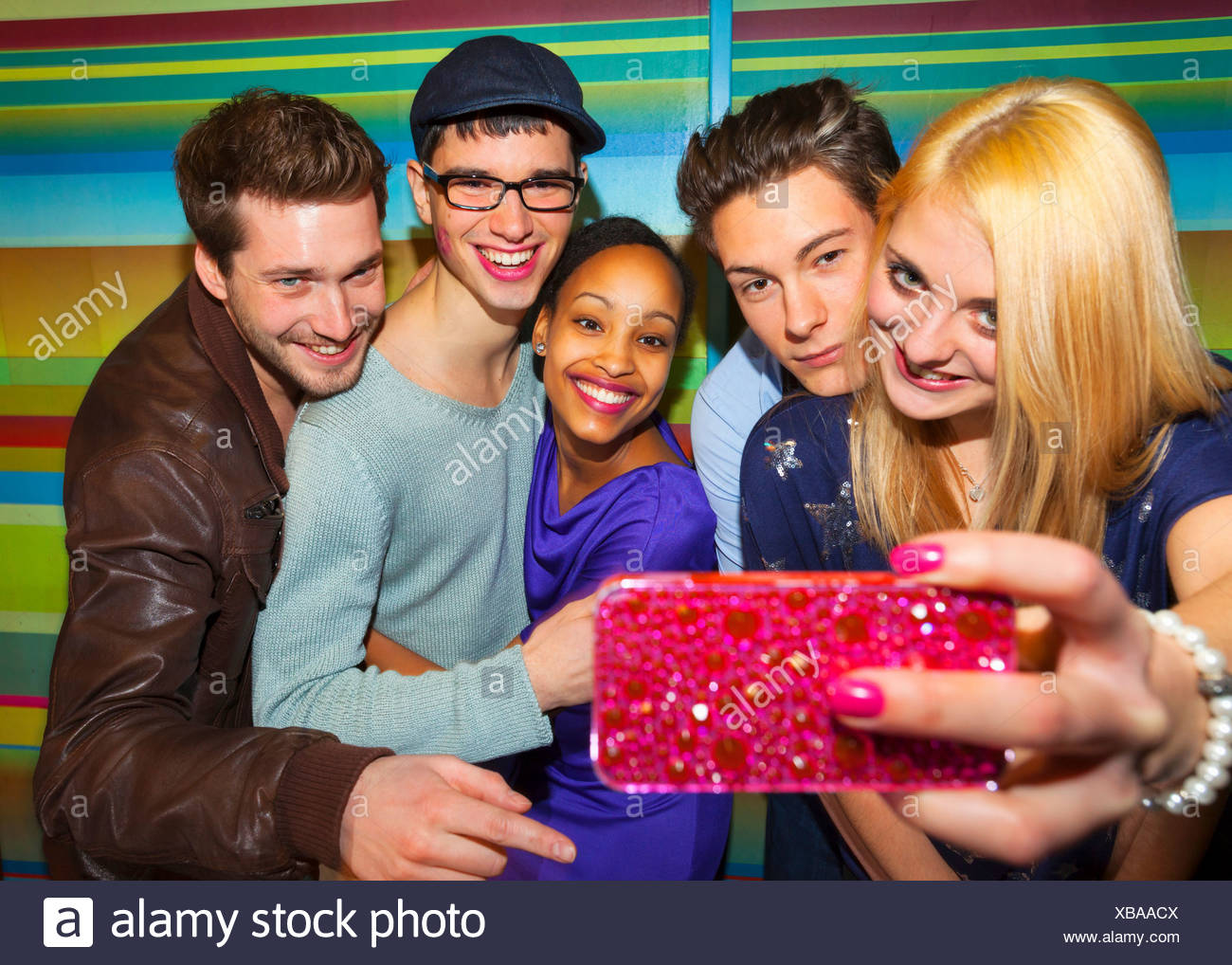 Group of young adults taking self portrait photograph using pink smartphone - Stock Image