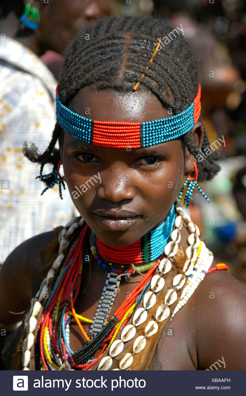 Girl wearing colorful bead head band and a necklace of kauri shells, portrait, at the markets in Dimeka, Ethiopia, Africa - Stock Image