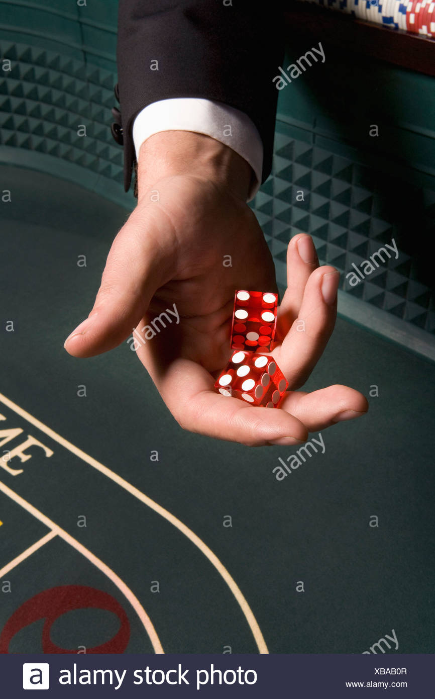 Man's hand holding dice at craps table - Stock Image