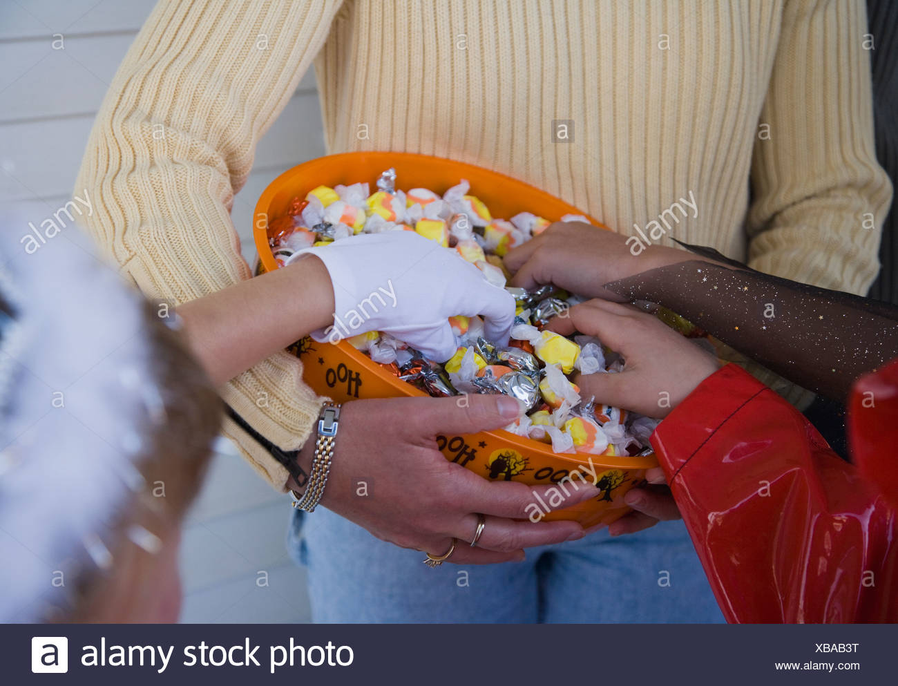 Children in Halloween costumes reaching into bowl of candy - Stock Image