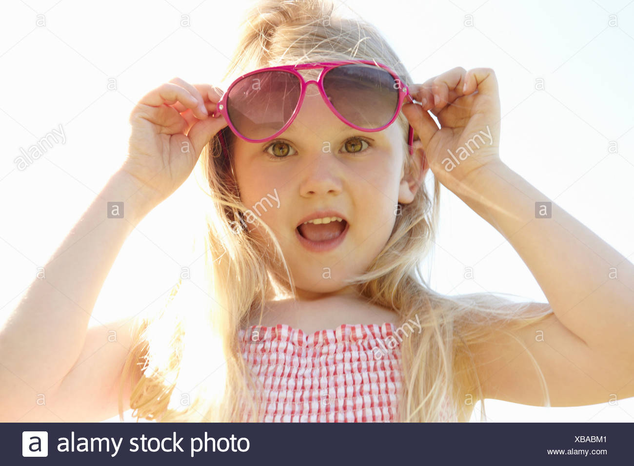 Child putting on sun glasses on hot sunny day - Stock Image