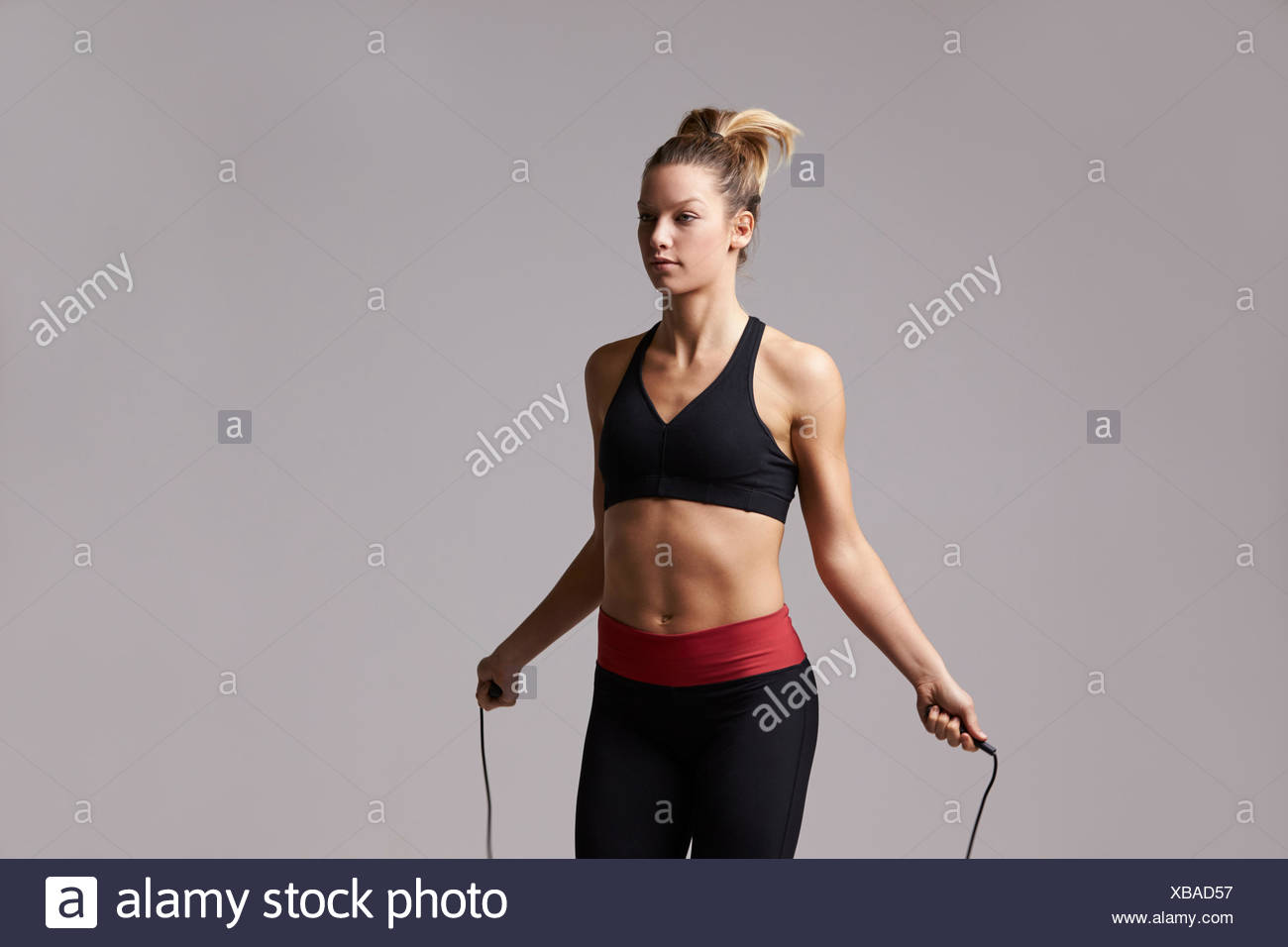Athletic blonde woman skipping rope, three quarter length - Stock Image