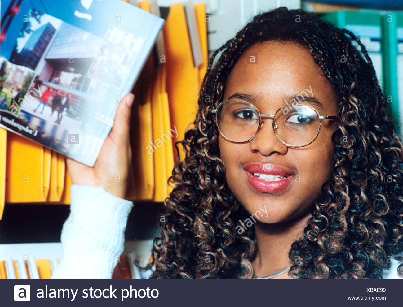 Young female student at further education college looking at higher  education prospectuses