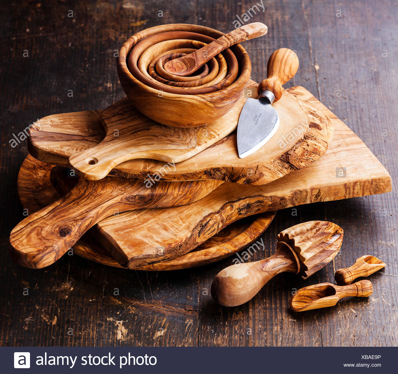 Olive wood tableware on dark wooden background - Stock Image