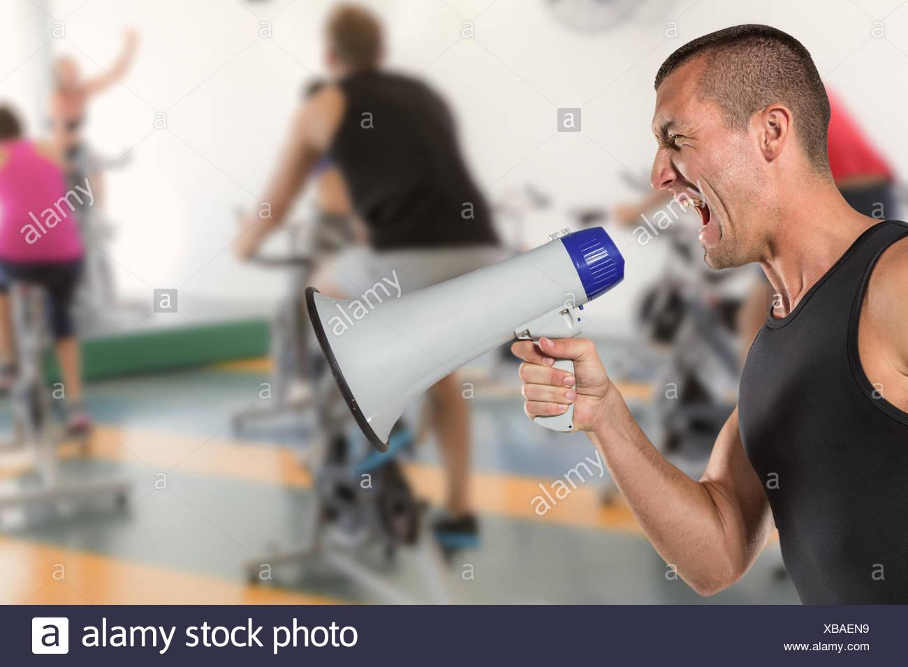 Composite image of irritated male trainer yelling through megaphone - Stock Image
