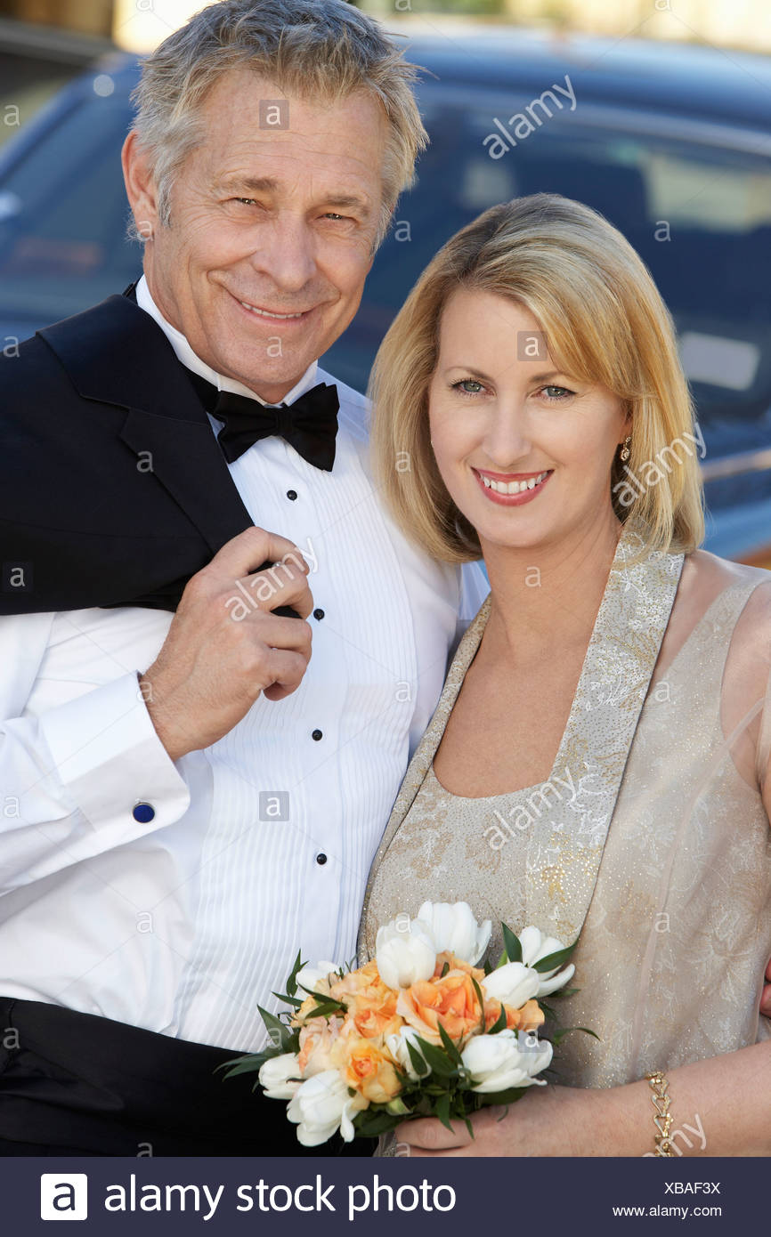 Middle-aged couple in formal wear in front of limousine, portrait - Stock Image