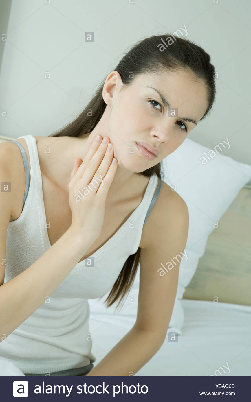 Woman touching throat and furrowing brow - Stock Image