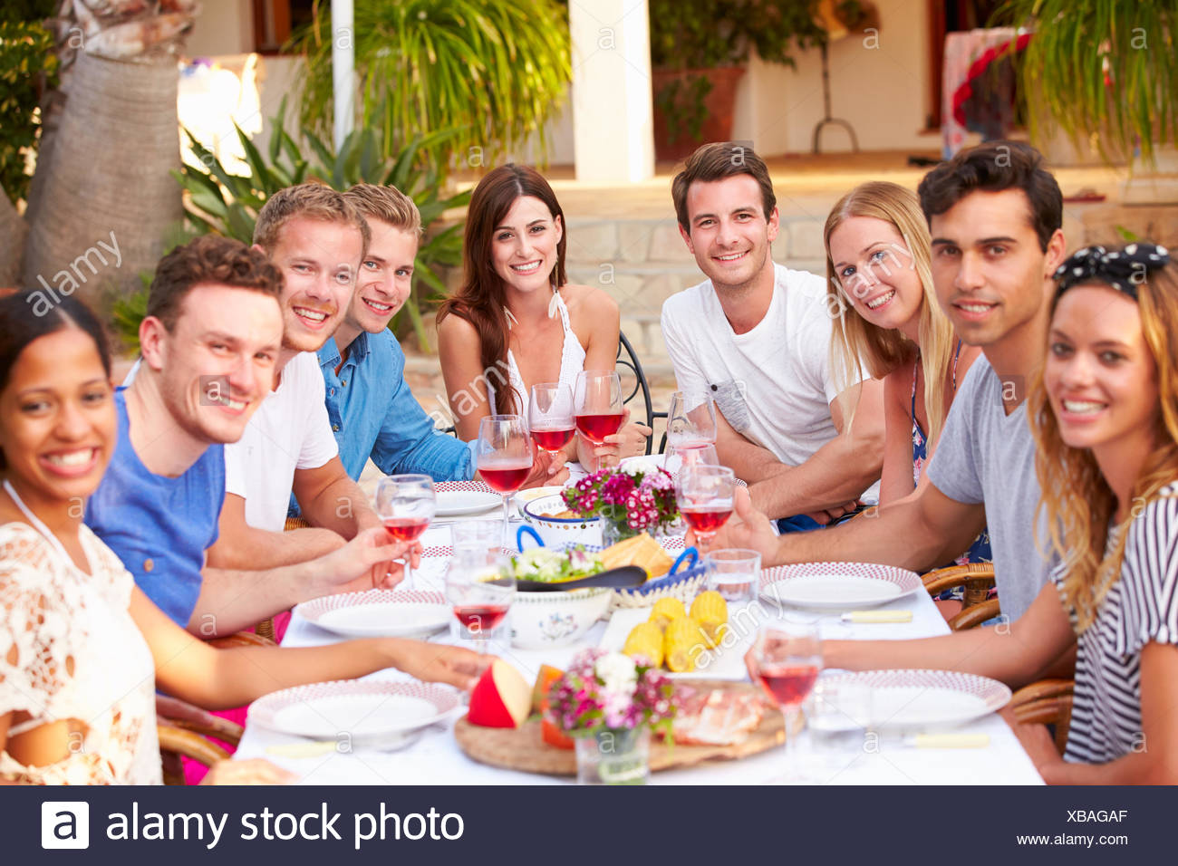 Large Group Of Young Friends Enjoying Outdoor Meal Together - Stock Image