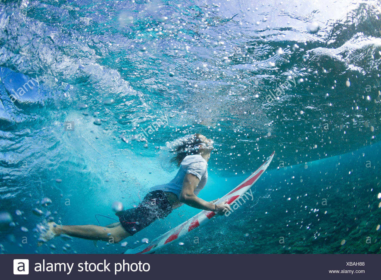 Underwater view of a surfer duck diving under a wave - Stock Image