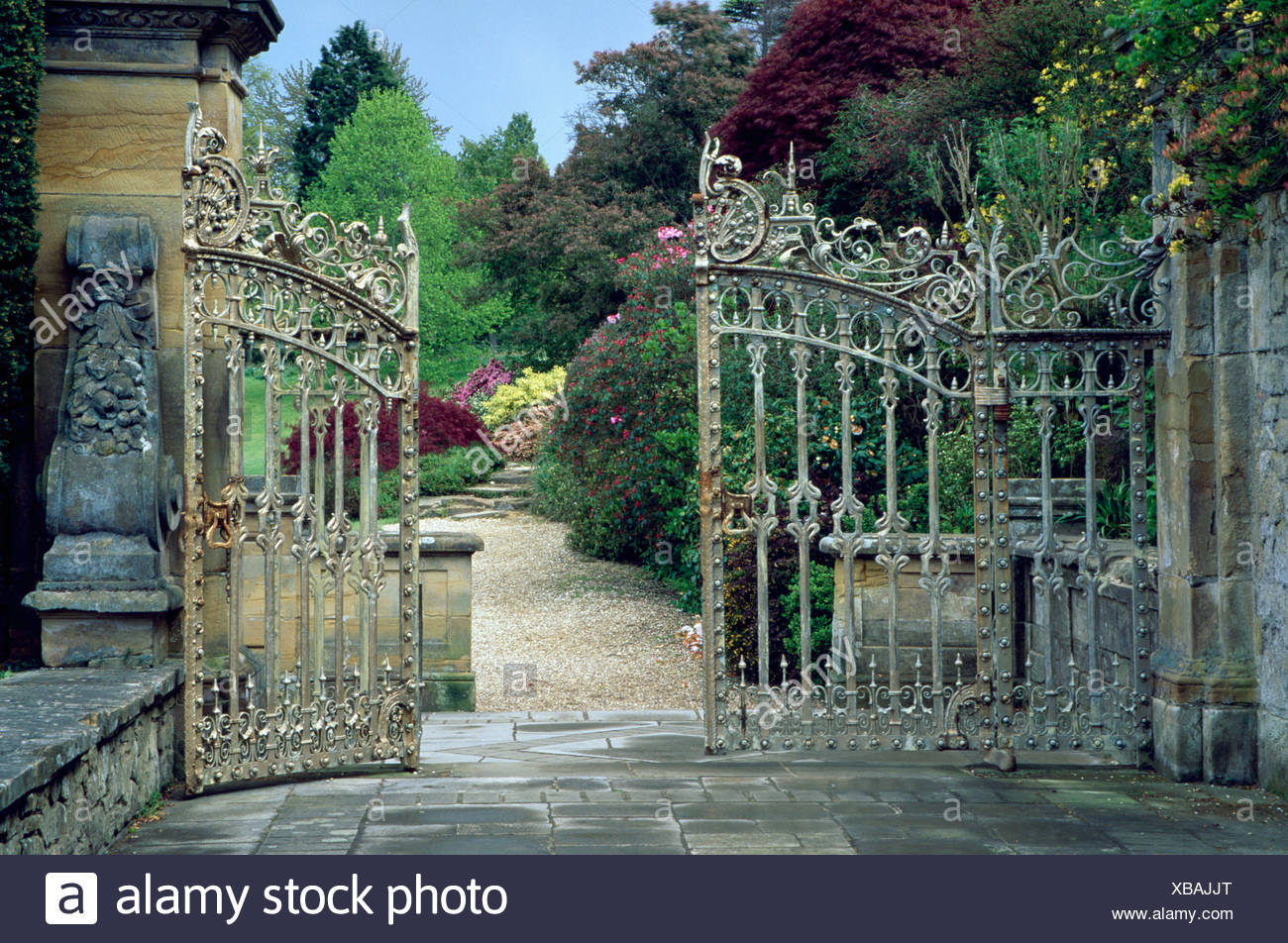 Large Iron Garden Gates Open With View Of Path And Summer Borders