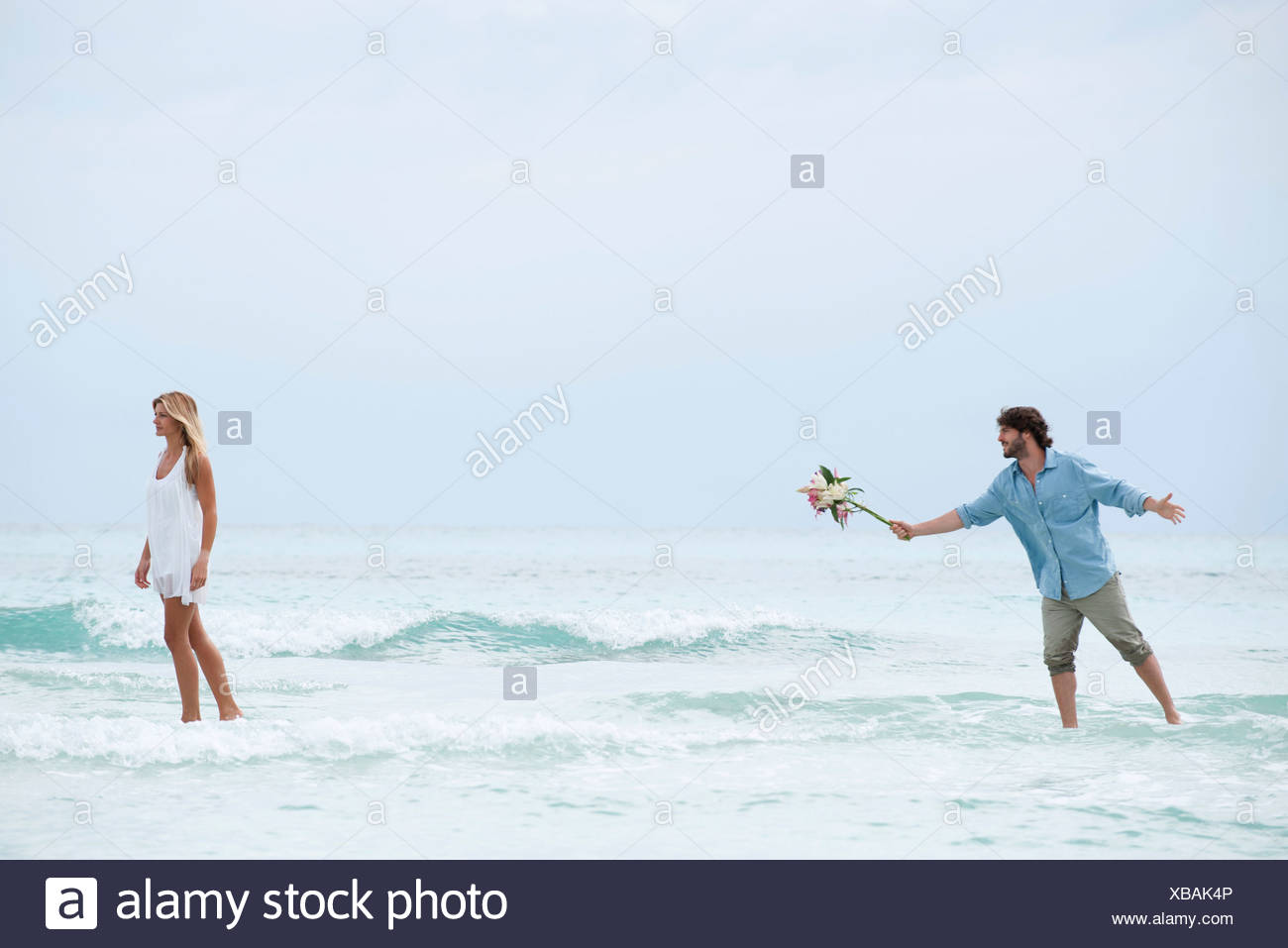 Couple standing in sea, woman walking away from man as he holds out a bouquet - Stock Image