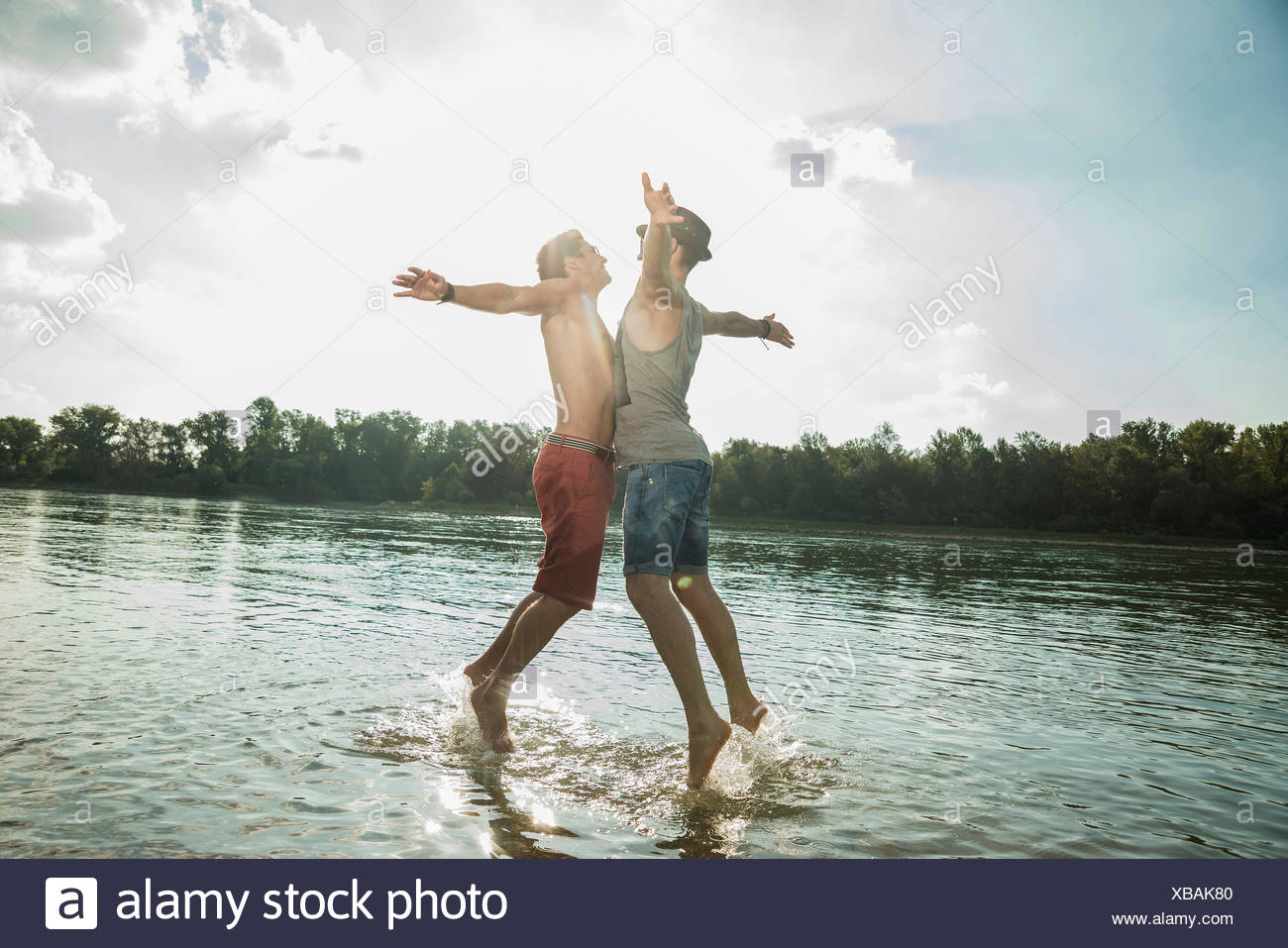 Young men chest bumping in lake - Stock Image
