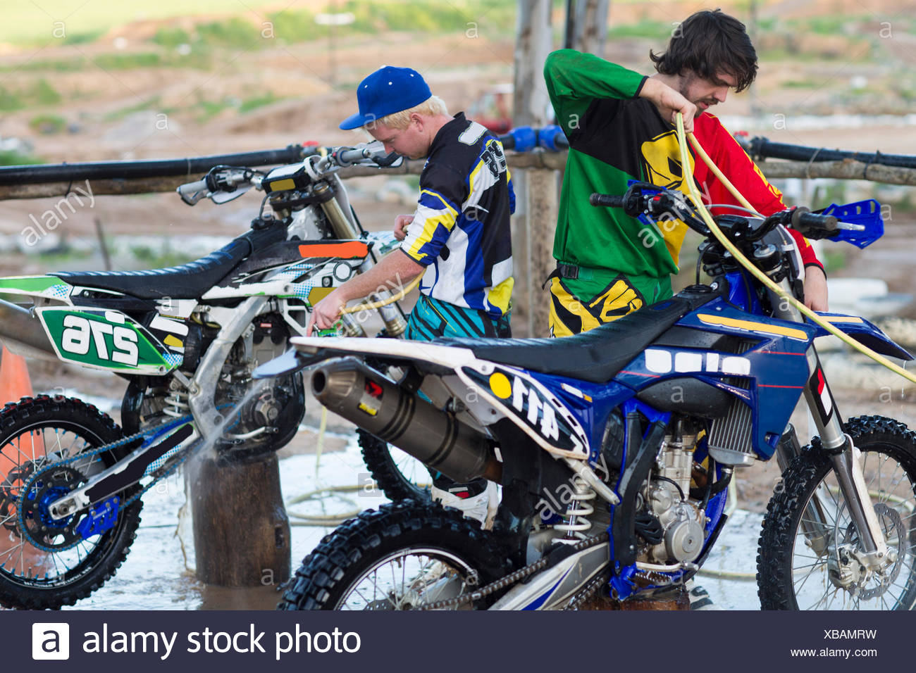 Two male motocross competitors cleaning motorcycles with water hoses - Stock Image