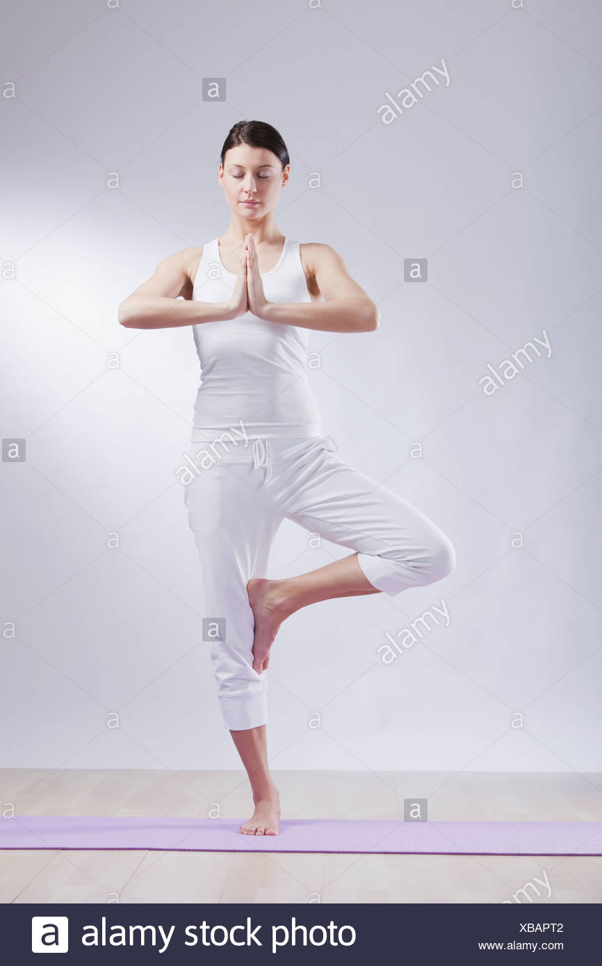Mid adult woman in tree pose against white background - Stock Image