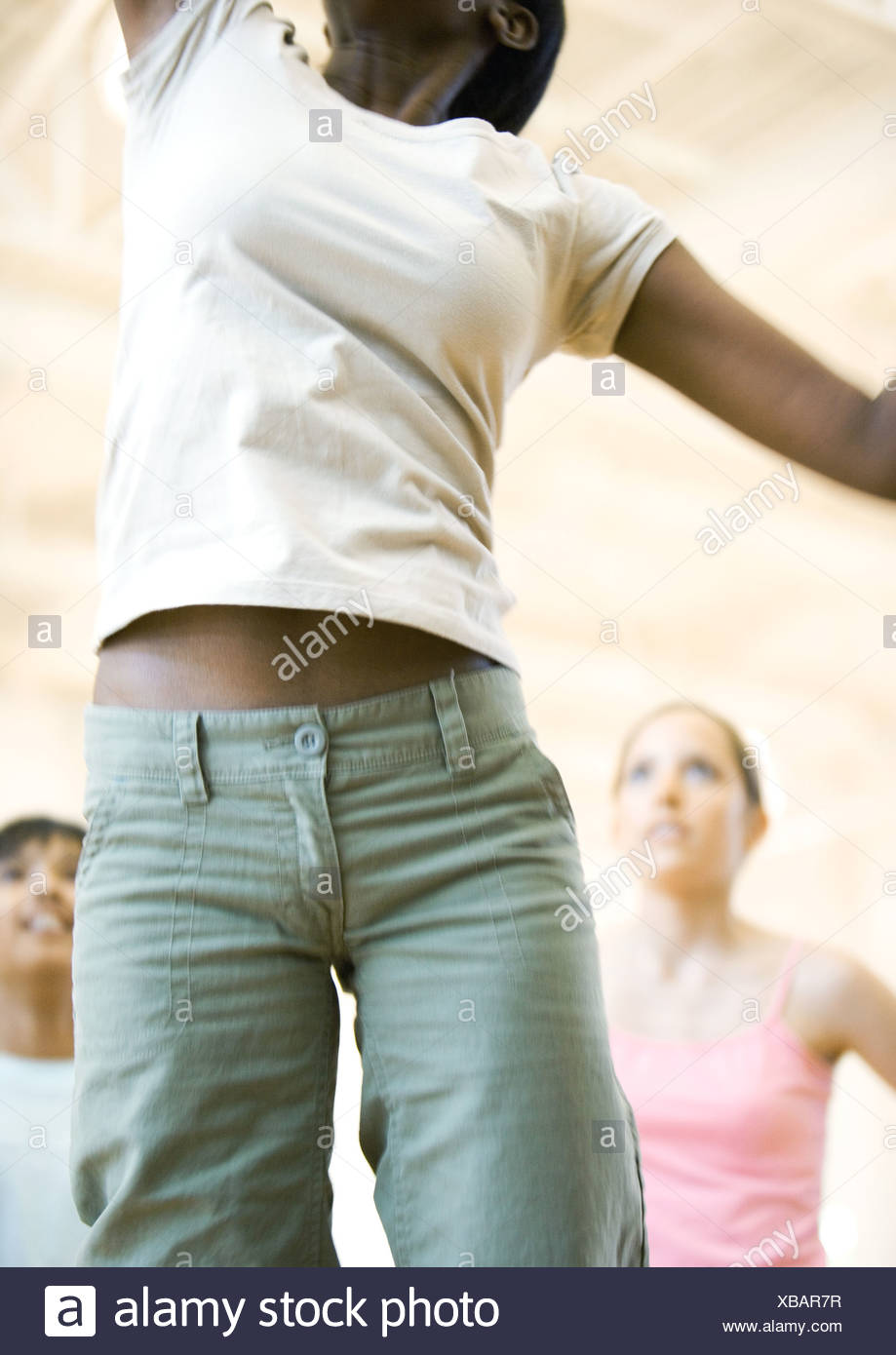 Teen girl jumping, mid section - Stock Image
