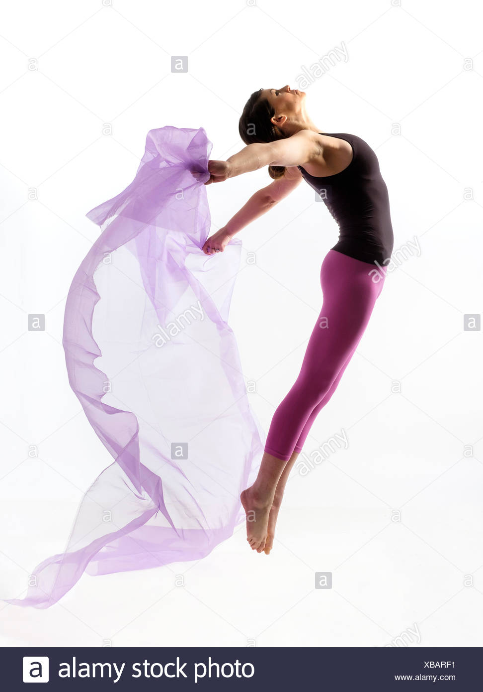 Woman with sheer fabric jumping - Stock Image